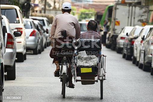 Yangon, Myanmar, March 17, 2019. A unidentified Sai Kaa driver is carrying a passenger on his side car among the narrow streets of Yangon, Myanmar. The Sai Kaa rickshaw is a type of tricycle designed to carry passengers on for hire basis and is widely used in southeast Asia.