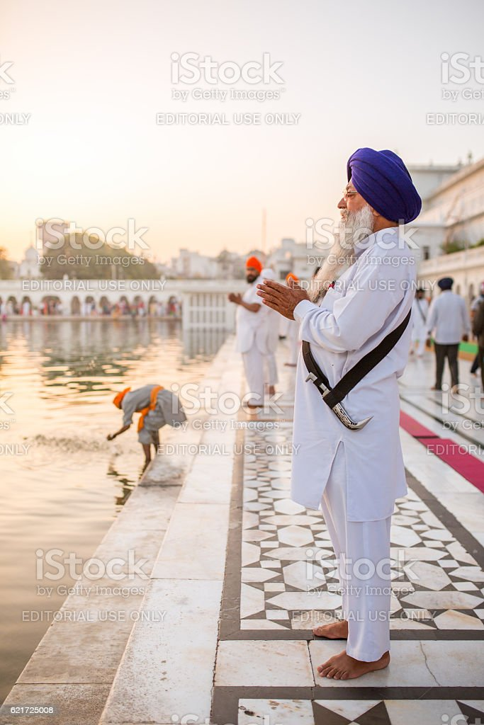 Unidentified sikh man praying near Golden temple in Amritsar stock photo