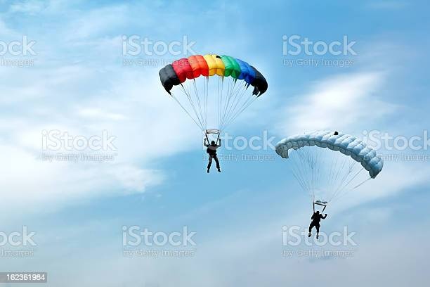 unidentified skydivers on blue sky two silhouettes of unidentified skydivers on blue sky Activity Stock Photo