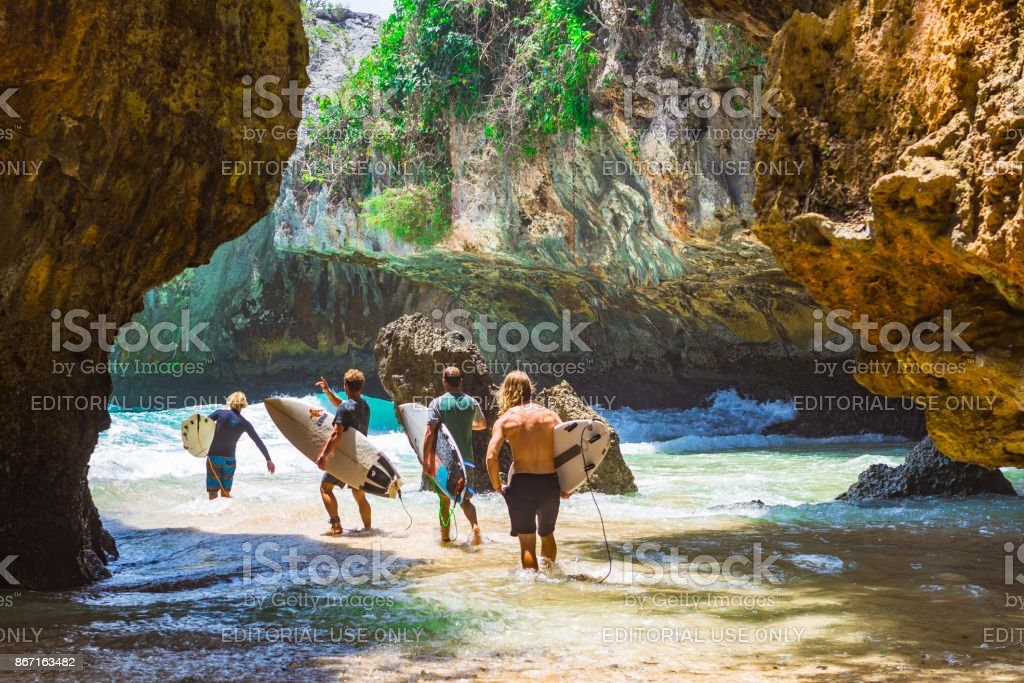 Unidentified surfers at Balangan beach, Bali. stock photo