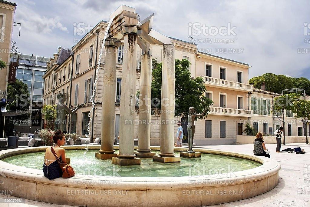 Unidentified tourists near fountain, Nimes, France stock photo
