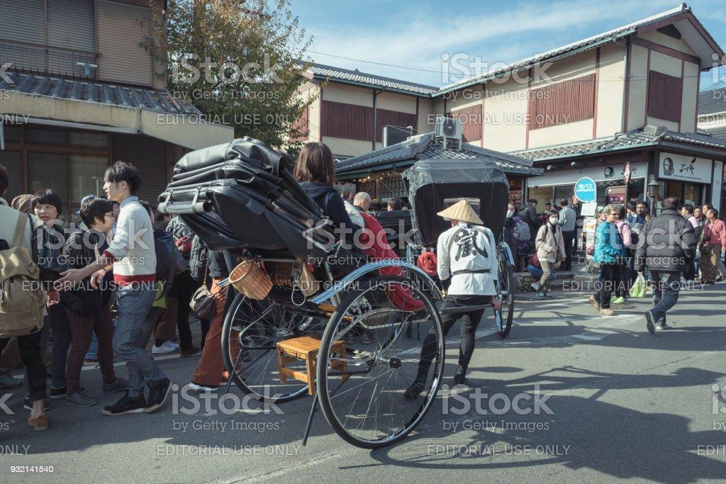Unidentified tourists on Japanese traditional rickshaw for sightseeing around Arashiyama in Kyoto stock photo