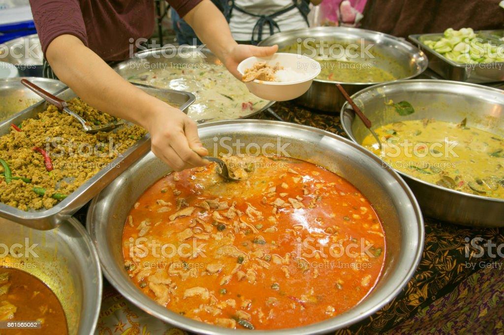 Unidentified vendors serve food at the streetside restaurant stock photo