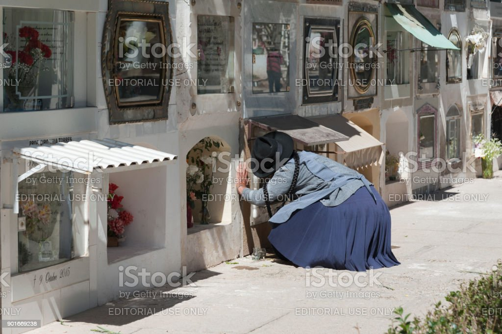 Unidentified woman near graves at Cementerio Municipal cemetery in Sucre, Bolivia stock photo