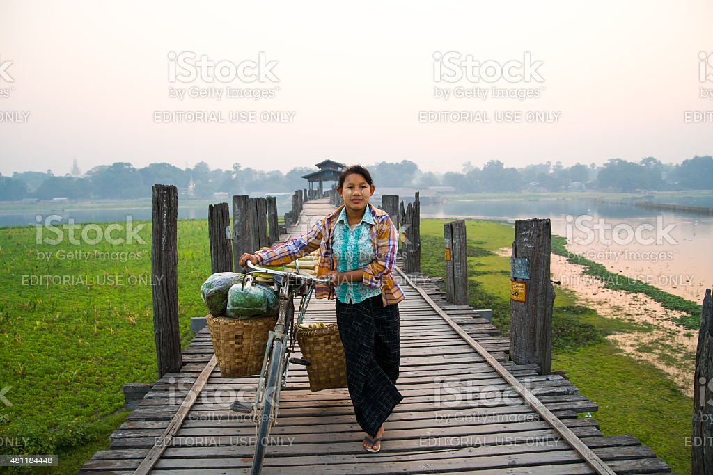 Unidentified woman with her bike on U-Bein bridge stock photo