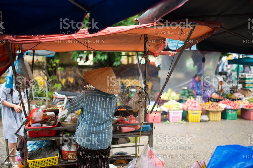 f43eba0ca5b Unidentified woman with typical vietnamese conical hats sell fresh  vegetables and meat skewers on a street
