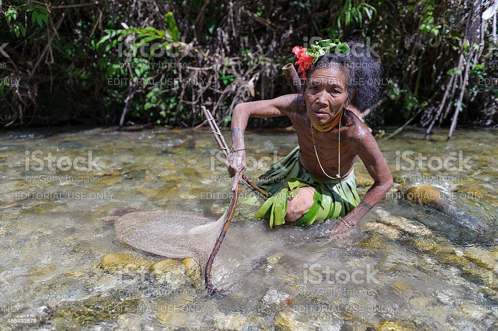 Unidentified women of Mentawai catching a fish. stock photo