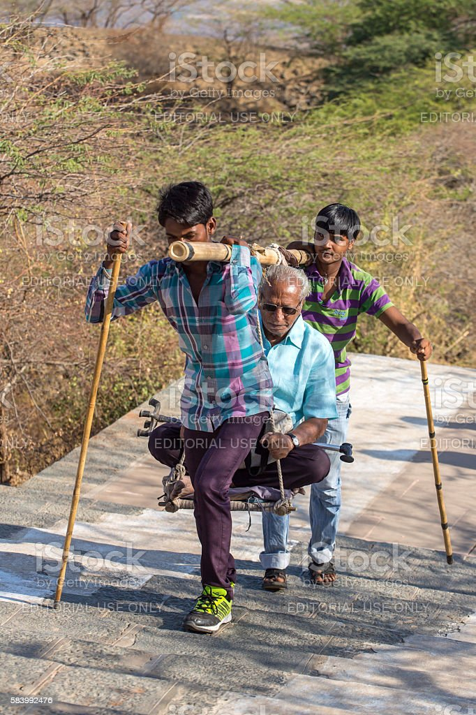 Unidentified workers, carry pilgrims to the Jain temples stock photo