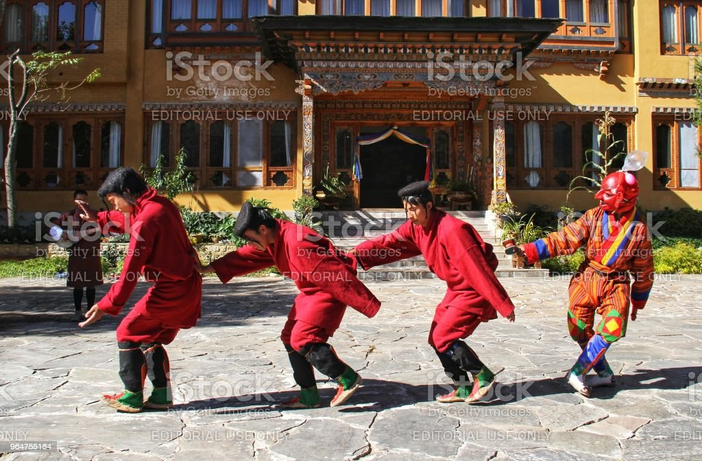 Unidentified young dancers in traditional Bhutanese dress performs traditional dance. Paro, Bhutan royalty-free stock photo
