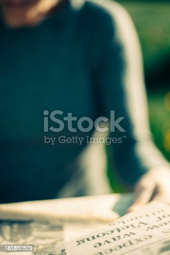 unidentified young woman reading an old newspaper outdoors in sunshine
