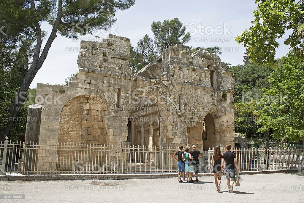 Unidetified tourists are looking at roman ruins in Nimes, France stock photo