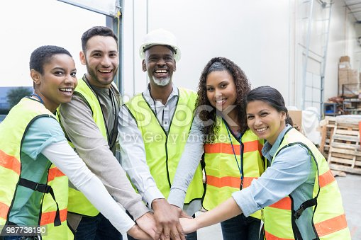 Confident diverse group of distribution warehouse employees have their hands together in unity. They are smiling at the camera.
