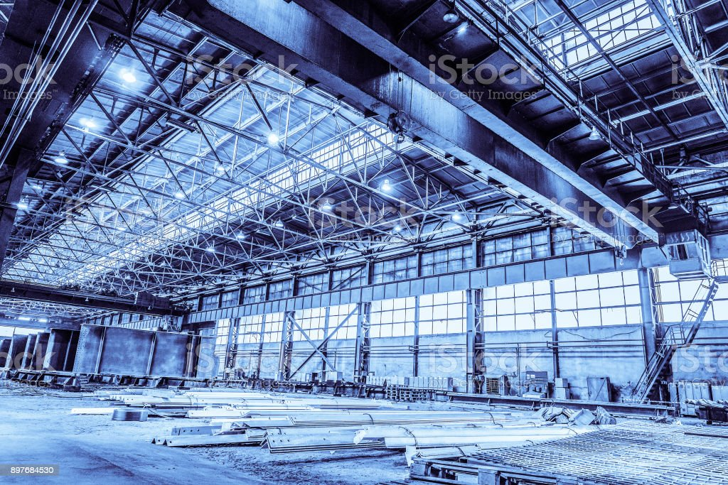 Unified standard typical span prefabricated of a steel frame production building. Industrial metalwork production hall with overhead cranes. Background in blue tone stock photo