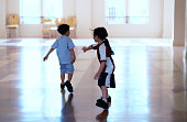 istock uniform girl and boy hold hand running in school hall 1209689483