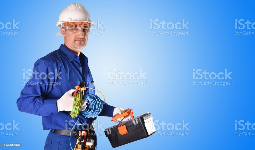 Uniformed electrician in blue overalls and safety protections and...