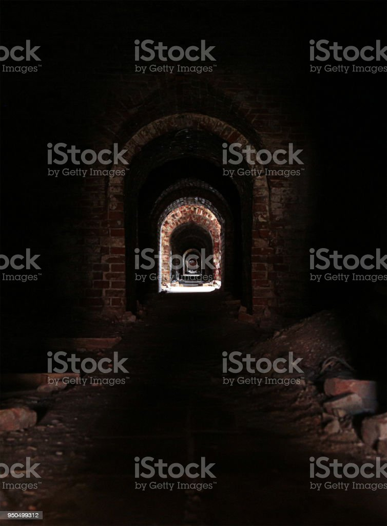 uninhabited horror horrible long corridor dark with a distant bright light, eerie catacombs with ruinous walls stock photo