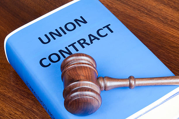Union contract and judge's gavel Judge's gavel on a Union contract book. labor union stock pictures, royalty-free photos & images