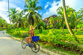 La Digue, Seychelles. Tourist woman on bicycle pointed Giant Union Rock, a monolith at Union Estate a former coconut and vanilla plantation near Anse Source d'Argent. Palm trees grove landscape.
