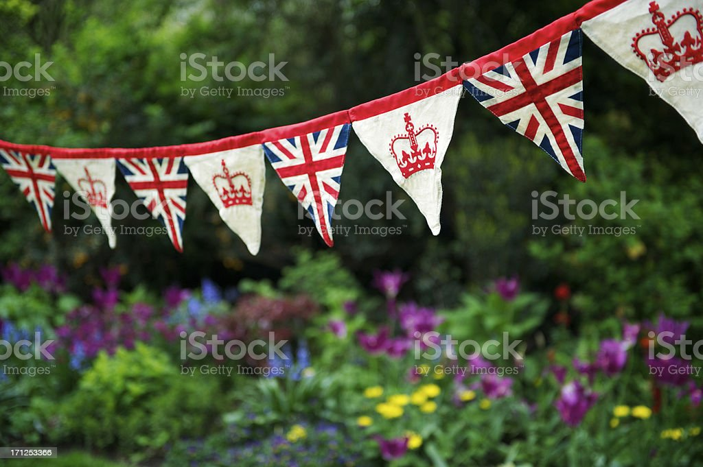 Union Jack British Flag Bunting Hangs Across English Garden royalty-free stock photo
