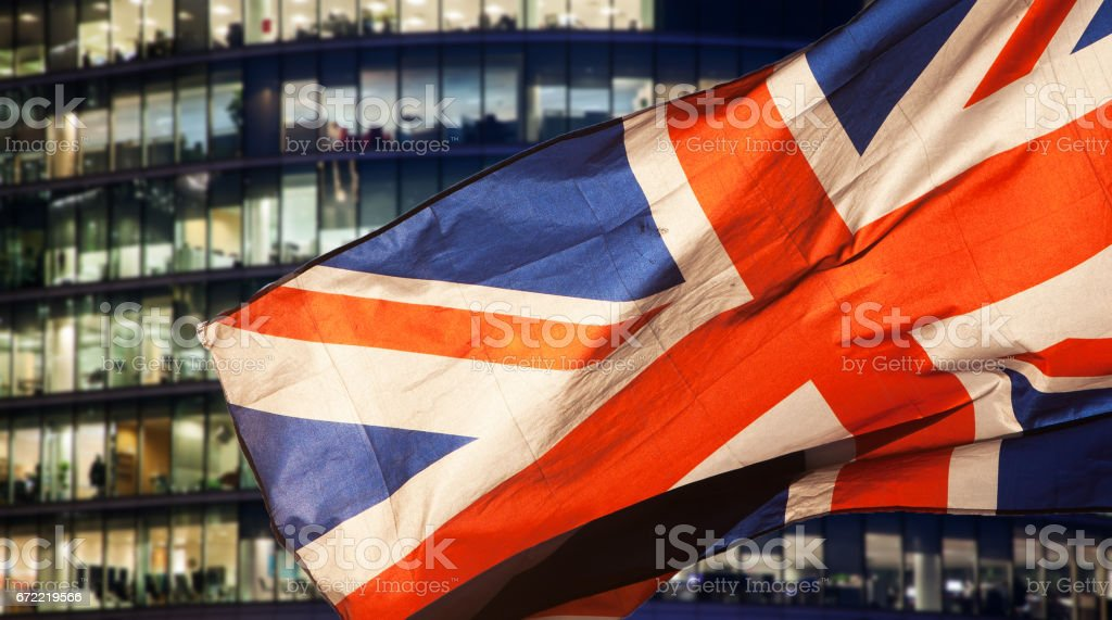 union jack flag over London financial district with iconic skyscrapers, UK prepares for elections after Brexit stock photo