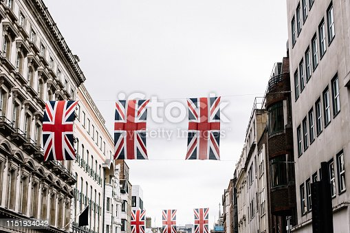 Union Jack flags hanging between two rows of buildings on Oxford Street in London, England