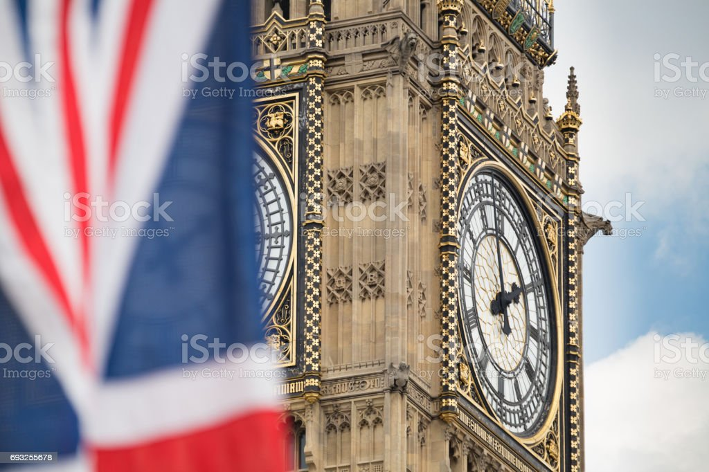 Union Jack fluttering in the wind with Big Ben in the background stock photo