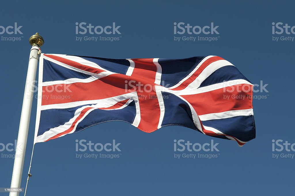 Union Jack Fluttering on Flag Pole in Blue Sky royalty-free stock photo