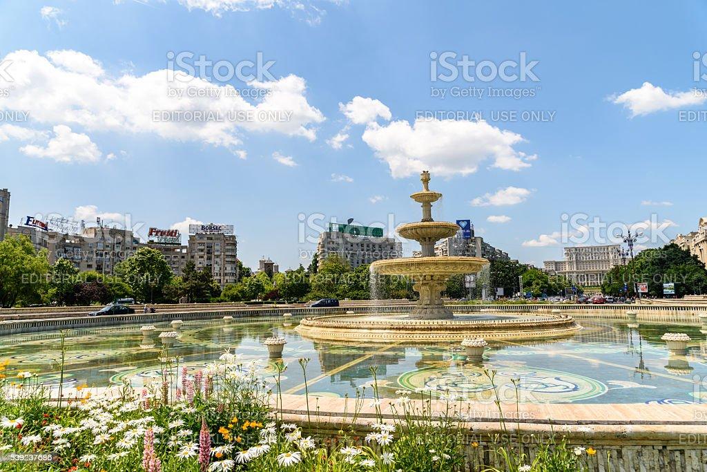 Fonte da Union Square e o Parlamento Palácio em Bucareste foto royalty-free