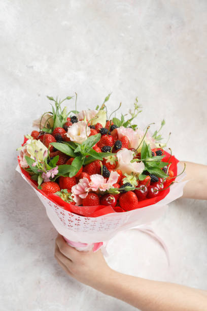 Unique bouquet of flowers, strawberries, cherries and blackberries in the hands of men on a marble background stock photo