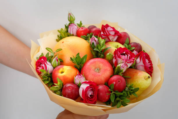 Unique festive bouquet consisting of apples, pears, plums, grapefruits and blooming roses in the hands of a girl stock photo