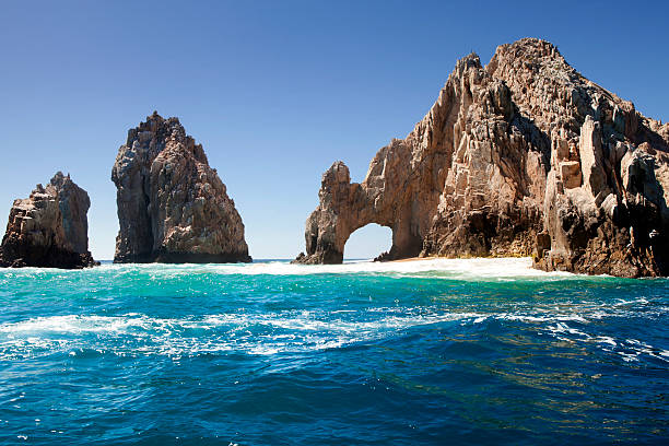 Unique jagged arch at Lands End in Cabo San Lucas Mexico The famous natural arch at Lands End in Cabo San Lucas, Mexico. natural arch stock pictures, royalty-free photos & images