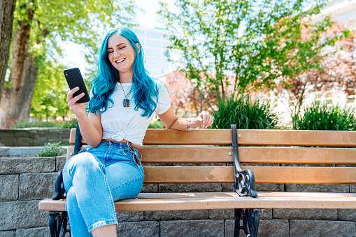 Unique Spunky Fashionable Young Woman with Fun Cute Teal Blue Green Dyed Hair Using Her Mobile Cell Smartphone to Text Friends, Check Her Email, Check Her Bank Account Balance, and Stay Connected While on the Go Outdoors in the Summer