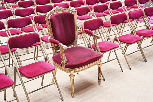 Unique throne or ceremonial armchair with velvet seat and golden details among many simple identical similar chairs. Uniqueness concept.