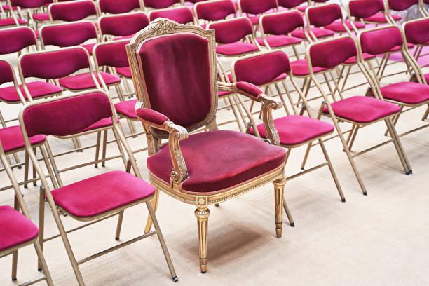 einzigartiger thron oder zeremonieller sessel mit samtsitz und goldenen details unter vielen einfachen identischen ähnlichen stühlen. einzigartigkeits- oder exklusivitätskonzept. - individualität stock-fotos und bilder
