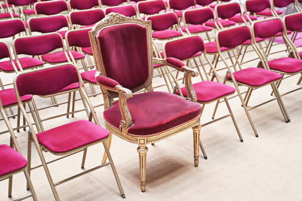 Unique throne or ceremonial armchair with velvet seat and golden details among many simple identical similar chairs. Uniqueness or exclusivity concept. stock photo