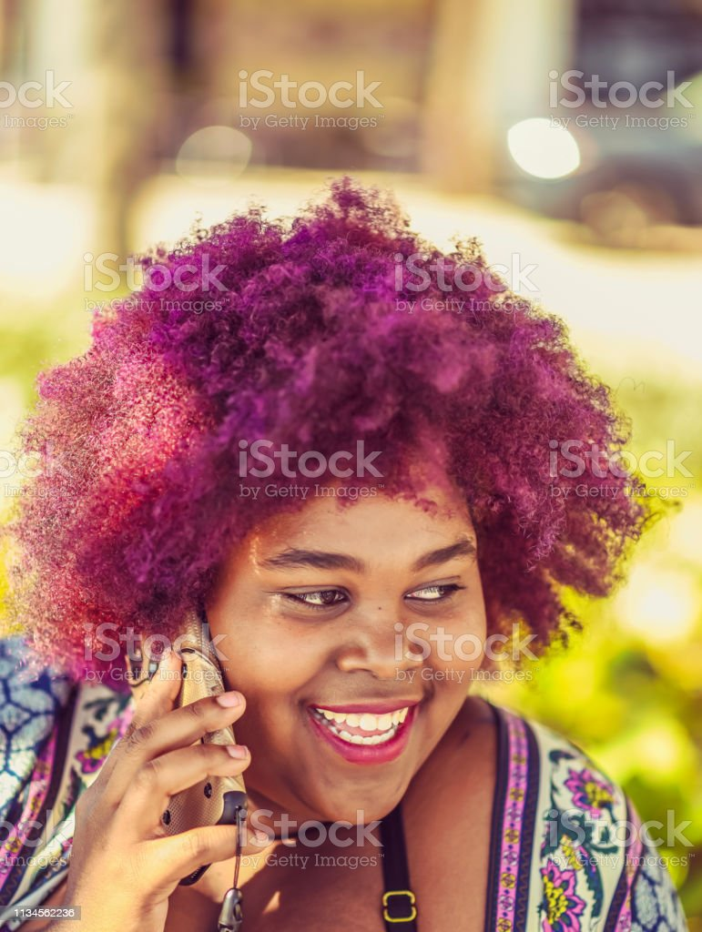 Young African American woman with big pink purple hair talks on a...