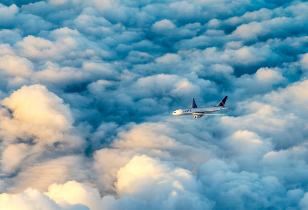 United airlines aircraft flies in the dark clouds with sunlight at the cockpit stock photo