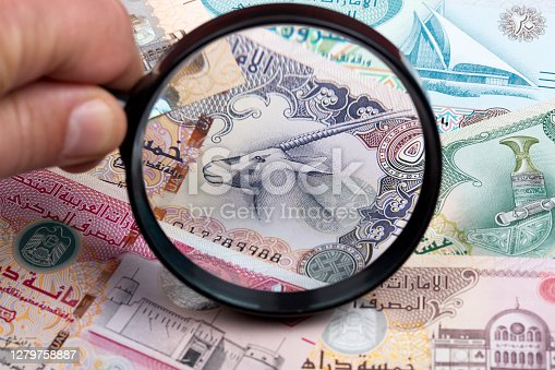 United Arab Emirates dirham in a magnifying glass a business background