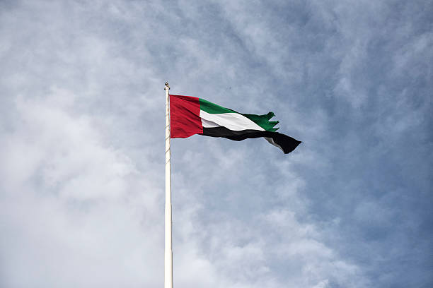united arab emirates flag against a cloudy blue sky - uae flag stok fotoğraflar ve resimler