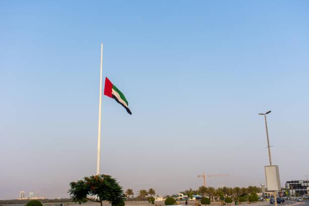 flaga zjednoczonych emiratów arabskich leci na pół masztu z powodu żałoby po śmierci władcy w zjednoczonych emiratach arabskich. - uae national day zdjęcia i obrazy z banku zdjęć