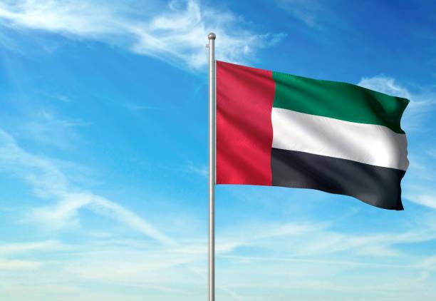 united arab emirates flag waving cloudy sky background - uae flag стоковые фото и изображения