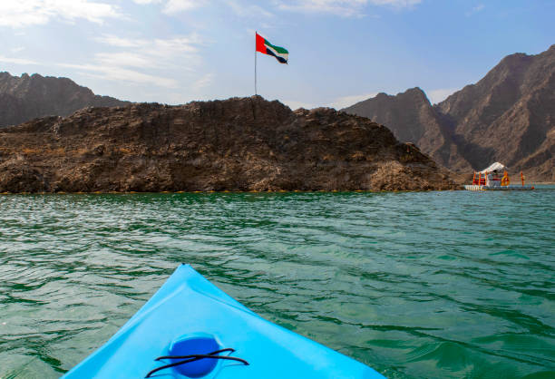 United Arab Emirates flag waving on top of a hill in the Middle of  Hatta lake with blue in color kayak on a foreground stock photo