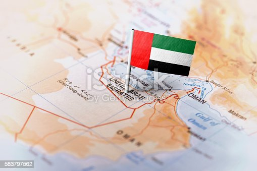 The flag of United Arab Emirates pinned on the map. Horizontal orientation. Macro photography.