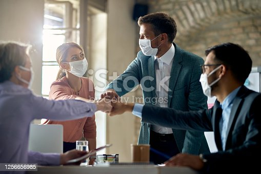 istock United business team with face masks colliding their fists on a meeting in the office. 1256656985