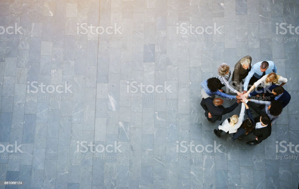 United colleagues standing in a huddle with their hands together stock photo