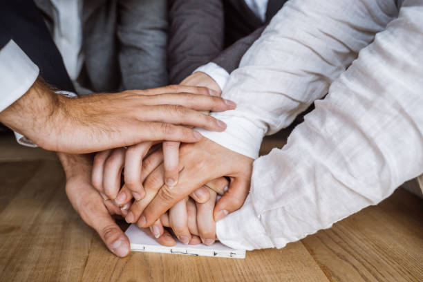 United hands of business team on workspace background stock photo