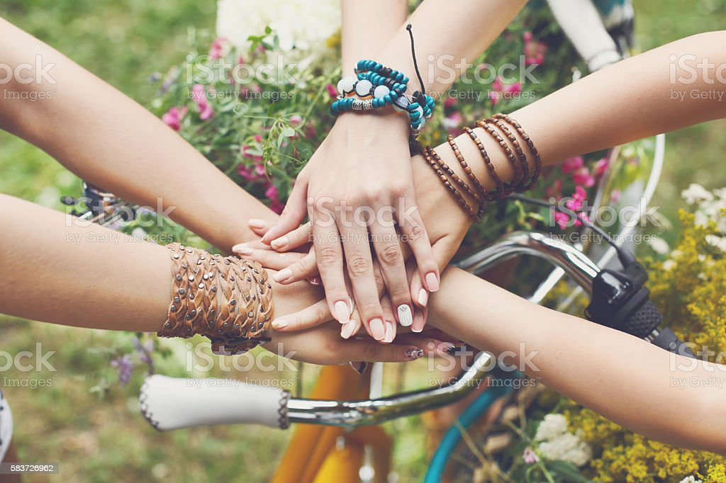 United hands of girlfriends closeup, young girls in boho bracelets - Photo