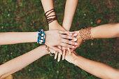 United hands of girlfriends closeup, young girls in boho bracelets