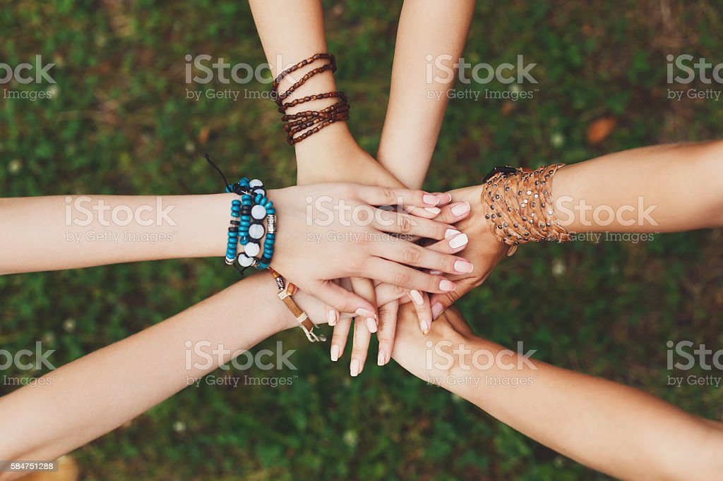 United hands of girlfriends closeup, young girls in boho bracelets stock photo