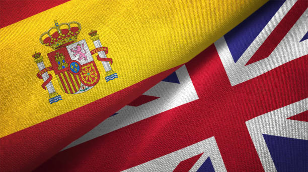 United Kingdom and Spain two flags together realations textile cloth fabric texture stock photo